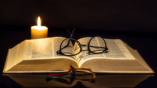Bible with candle and glasses